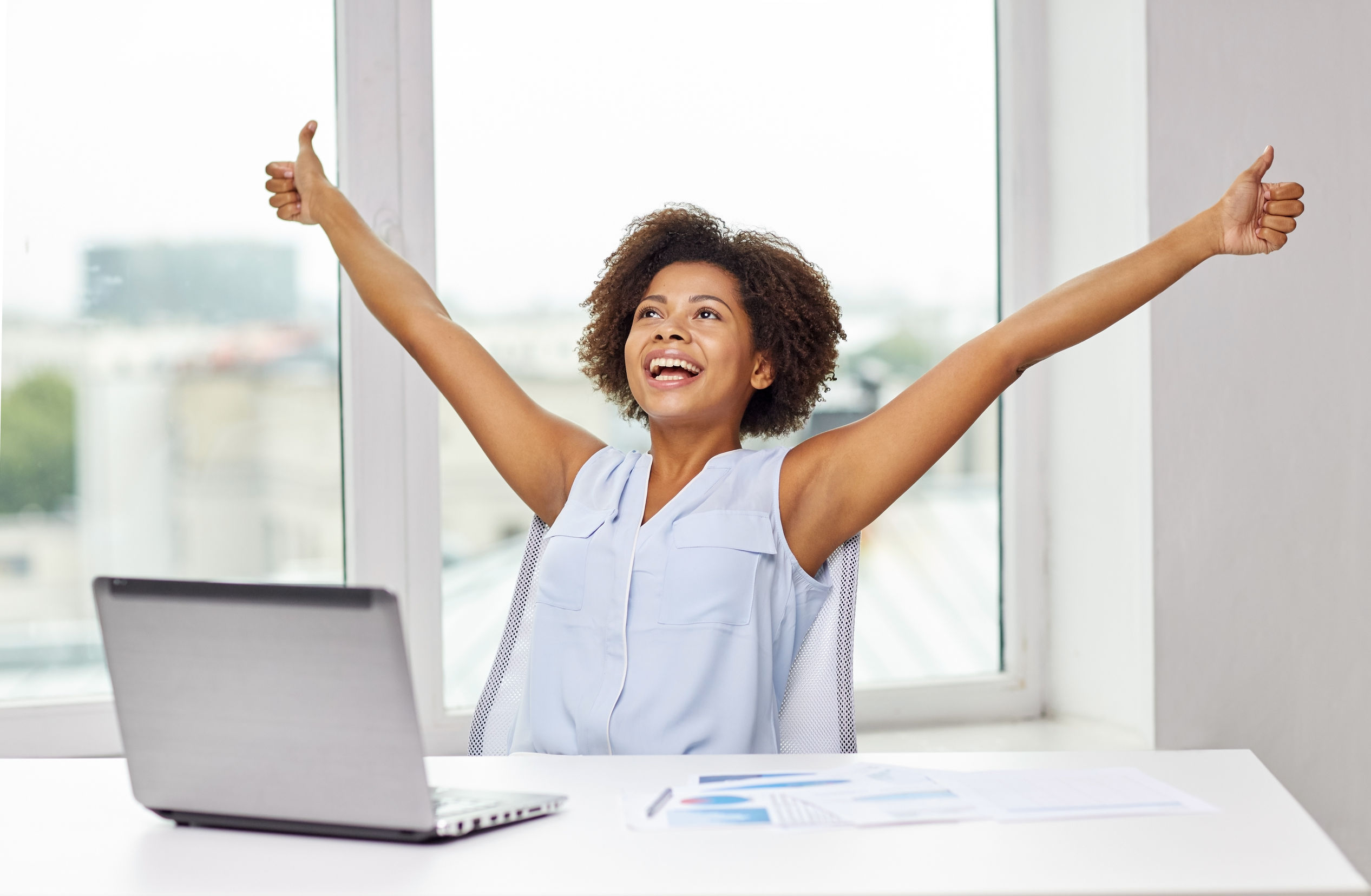 62066104 - education, business, success, gesture and technology concept - happy african american businesswoman or student with laptop computer and papers showing thumbs up and celebrating triumph at office